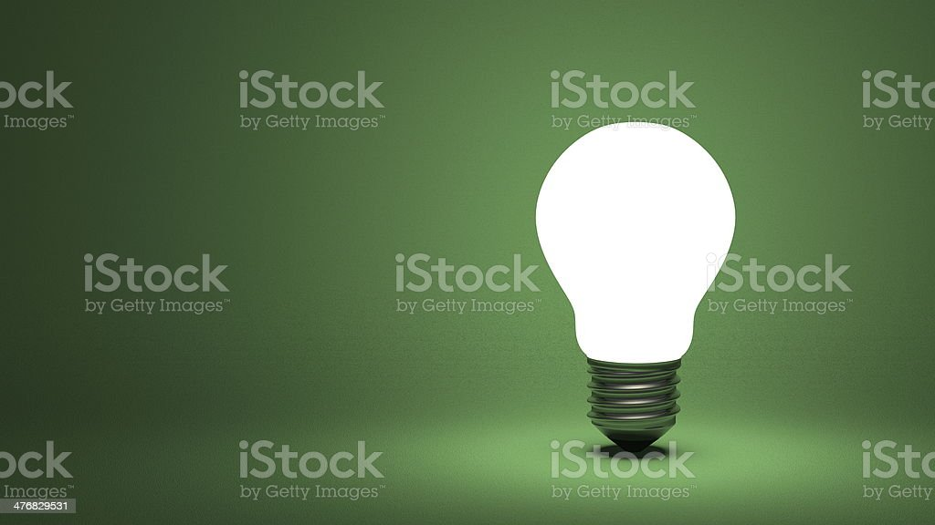 Glowing light bulb on green stock photo