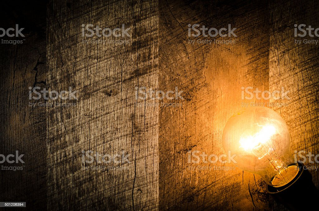 Glowing light bulb on wooden background stock photo