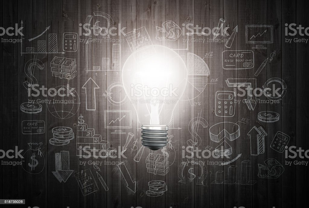 Glowing light bulb on wooden wall with drawing charts and stock photo