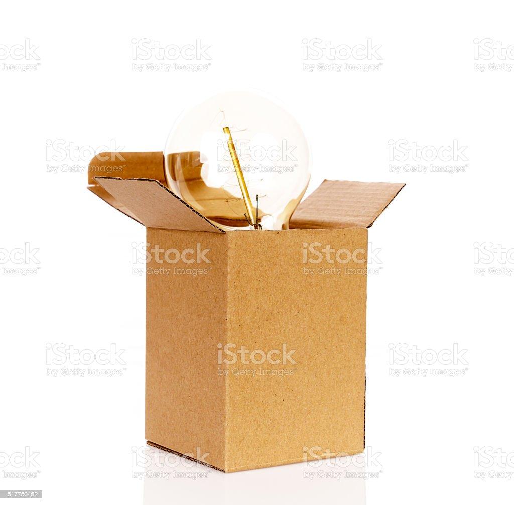 Glowing light bulb over open cardboard box stock photo