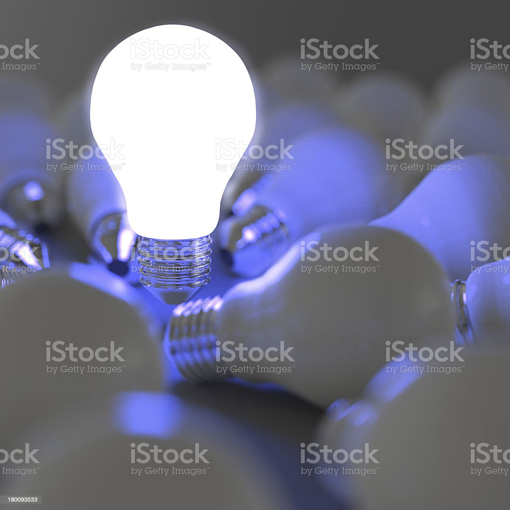 Glowing light bulb surrounded by other light bulbs stock photo