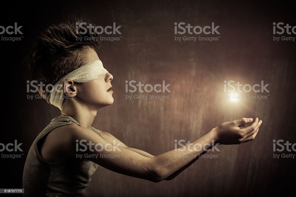 Glowing Light Over the Open Hands of a Blind Boy stock photo
