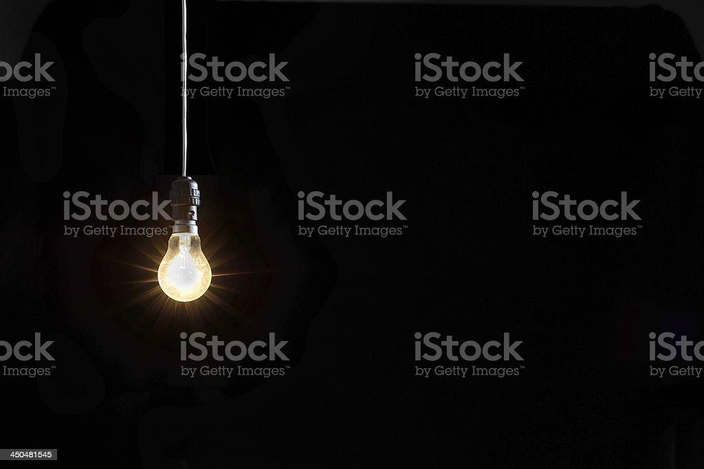 Glowing lightbulb against black background royalty-free stock photo