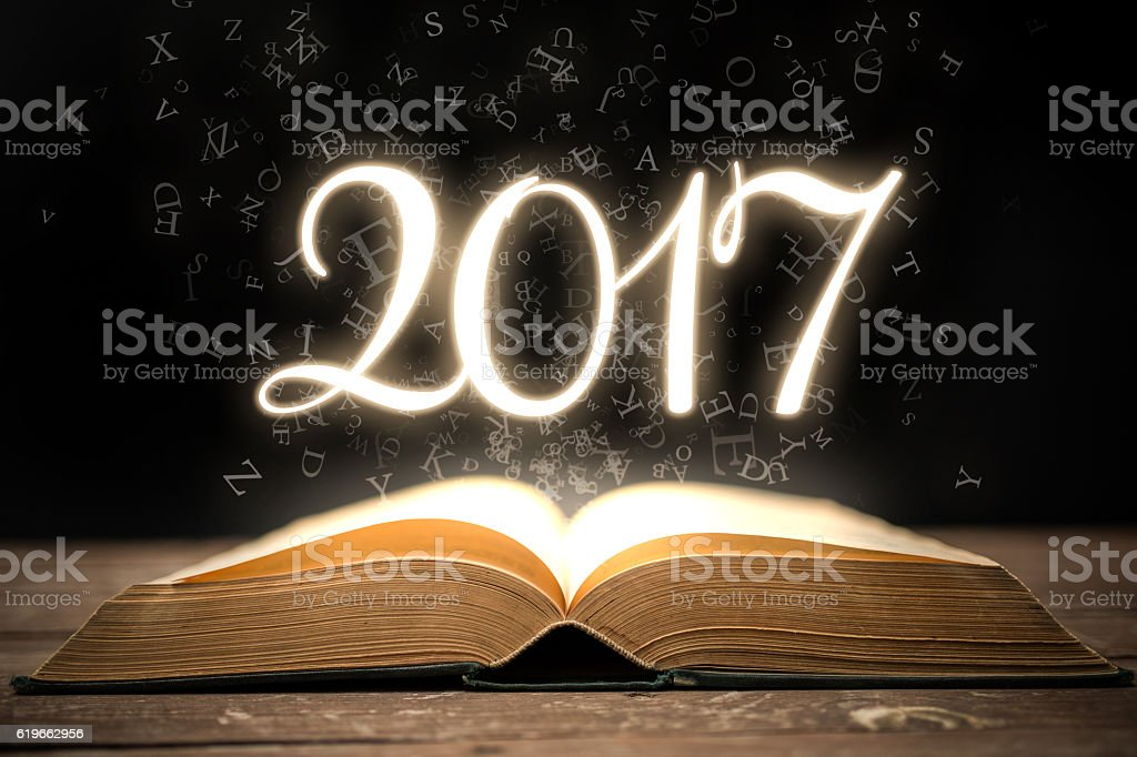 Glowing new year 2017 with magic book stock photo