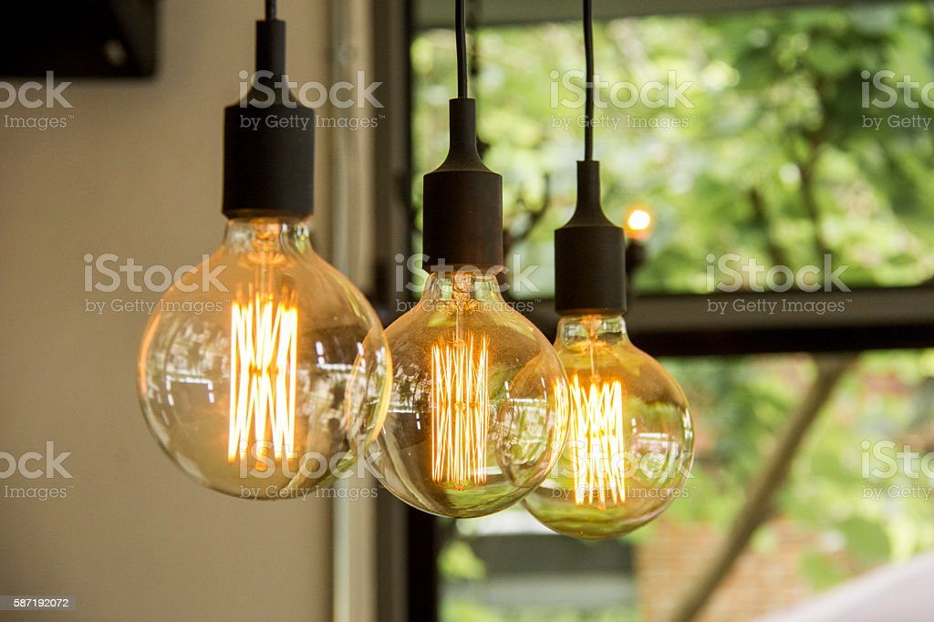 Glowing retro light bulbs hanging from ceiling stock photo