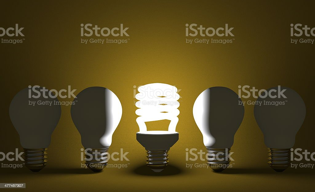 Glowing spiral light bulb and dead tungsten ones on yellow stock photo