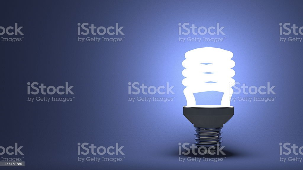Glowing spiral light bulb on blue stock photo