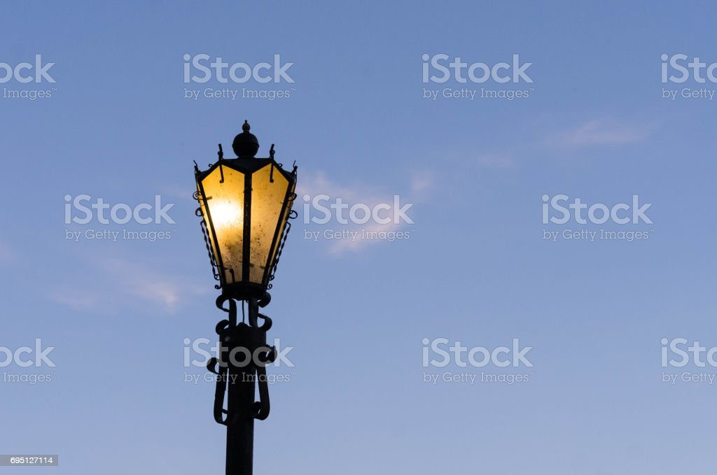 Glowing street lamp against a blue sky. stock photo