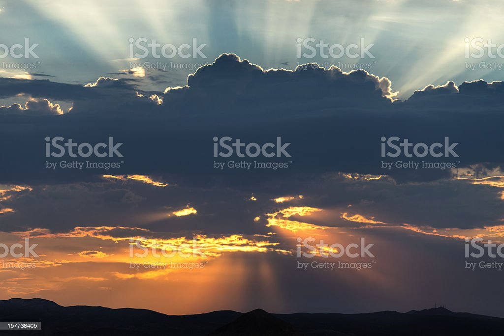Glowing Sun and Sunbeams Behind Clouds royalty-free stock photo