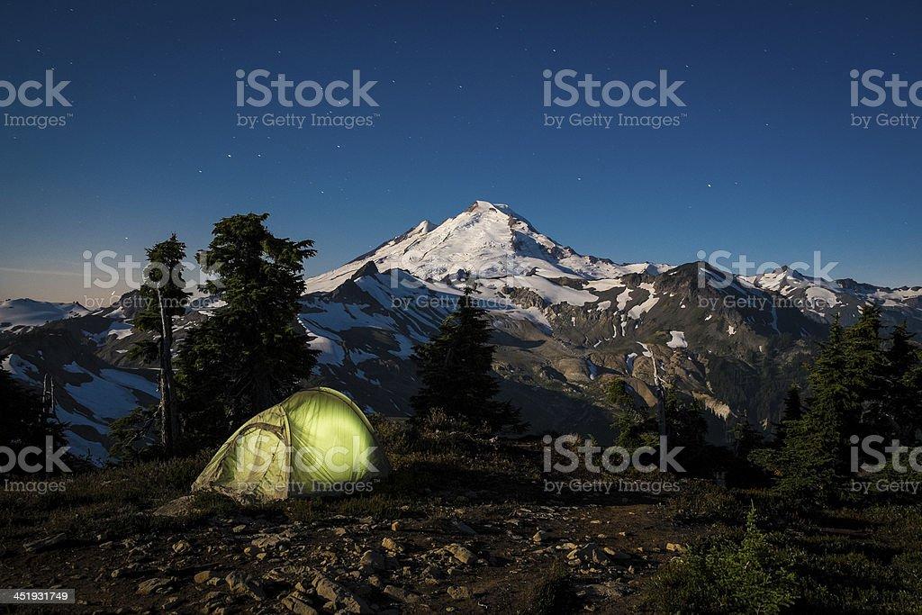 Glowing tent at night beneath Mount Baker, Washington state stock photo