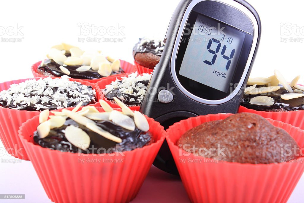 Glucometer and chocolate muffins in red cups stock photo
