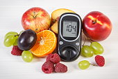 Glucometer and fresh fruits, diabetes and healthy nutrition
