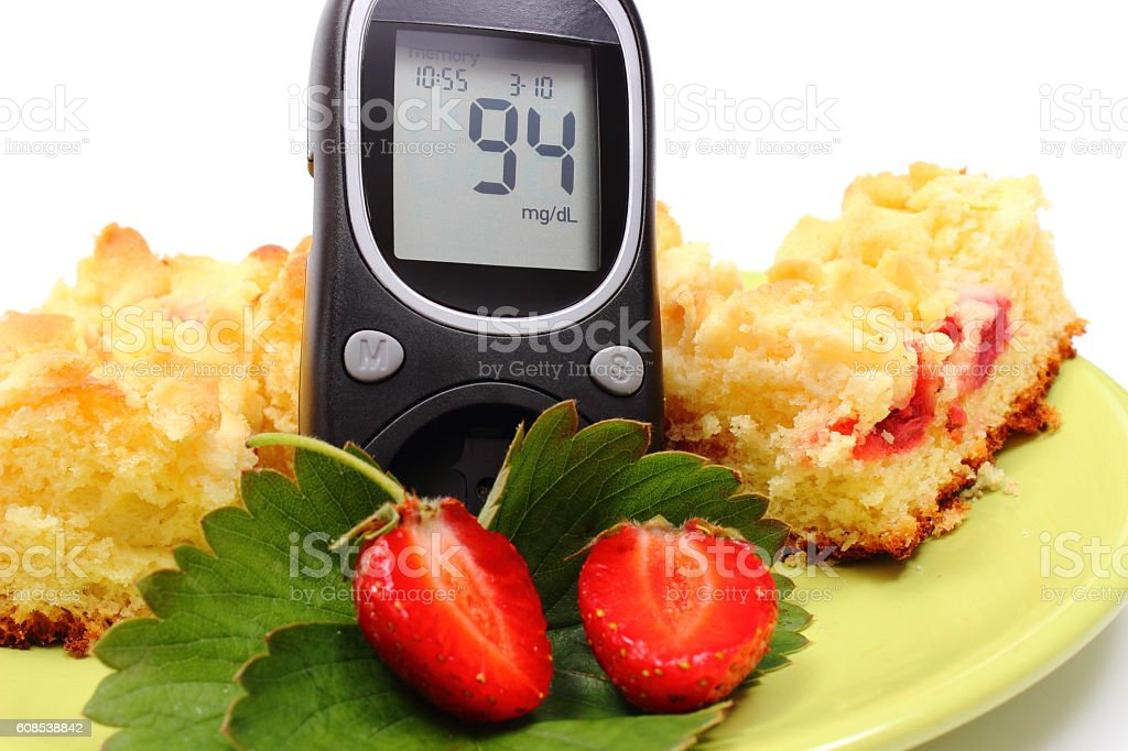 Glucometer and pieces of yeast cake with strawberries stock photo
