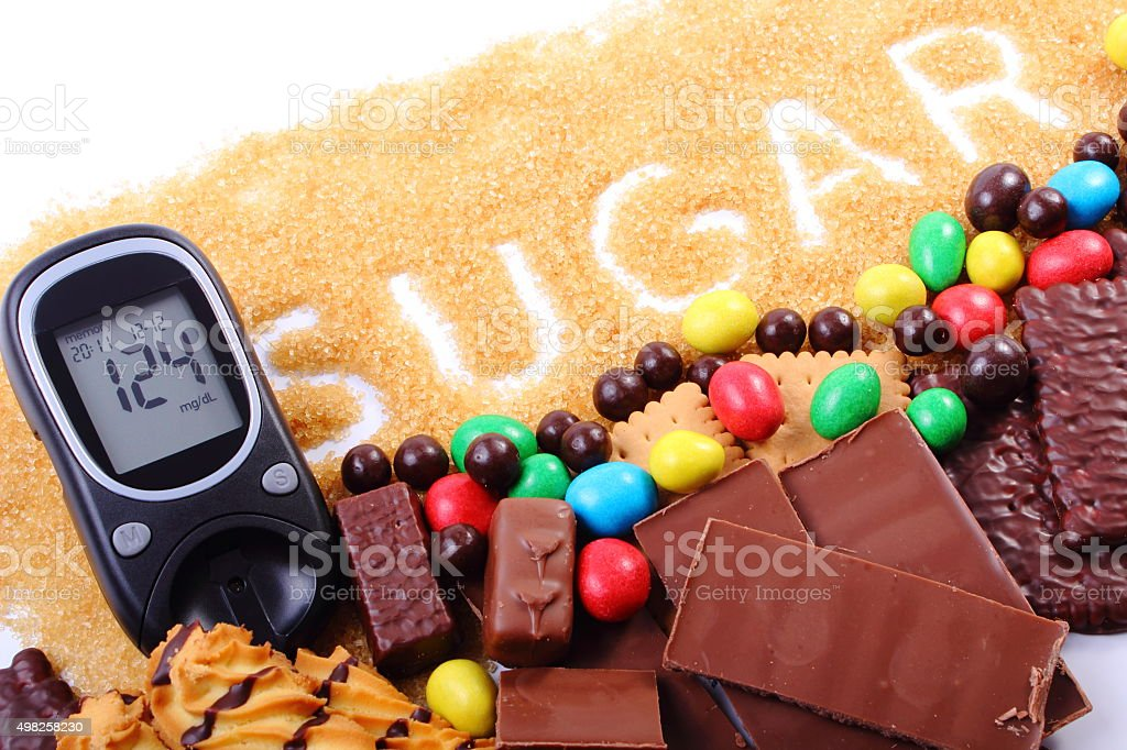 Glucometer, cane brown sugar and a lot of sweets stock photo