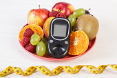 Glucometer, fresh fruits on plate and centimeter, diabetes