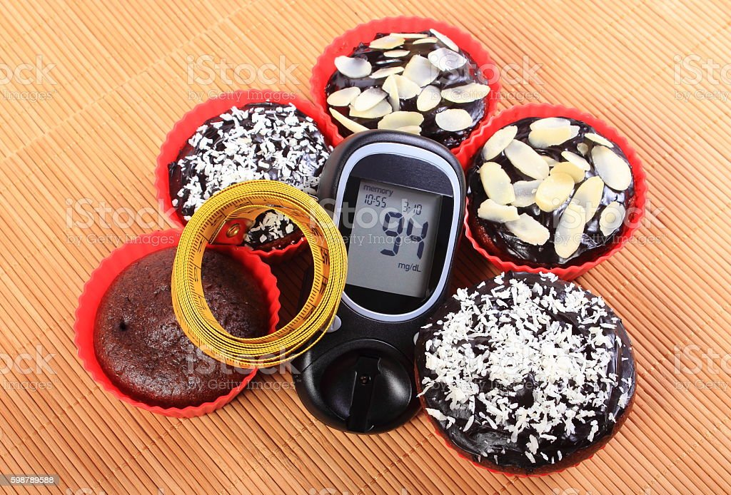 Glucometer, muffins in red cups and tape measure stock photo