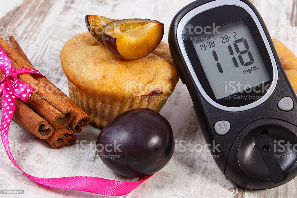 Glucometer, muffins with plums and cinnamon sticks on wooden background stock photo