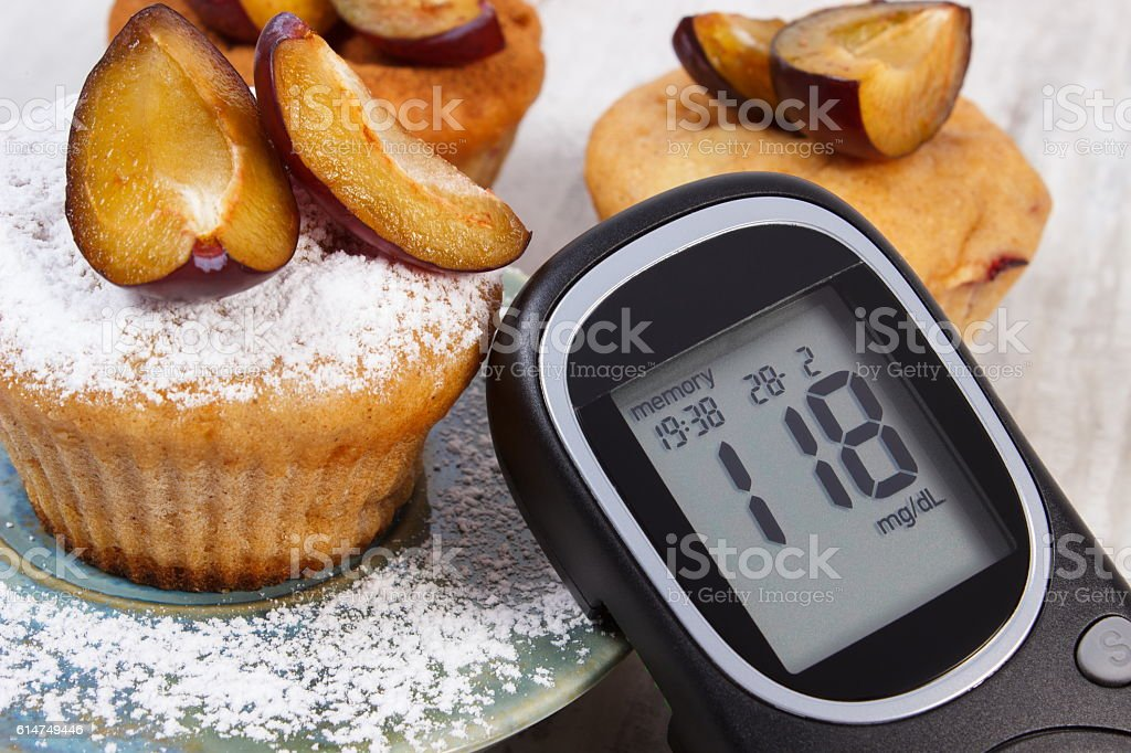 Glucometer, muffins with plums and powdered sugar stock photo