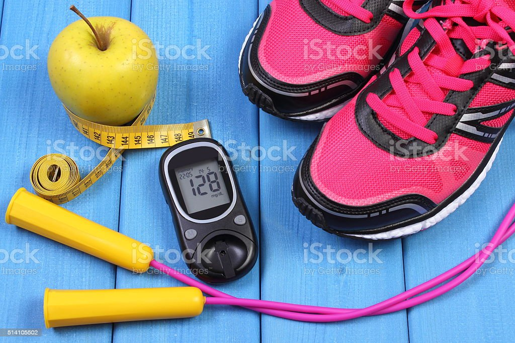 Glucometer, sport shoes, fresh apple and accessories for fitness stock photo