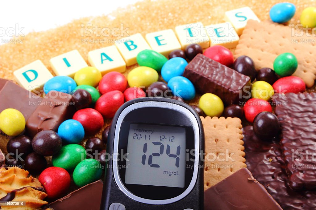 Glucometer, sweets and cane brown sugar with word diabetes stock photo