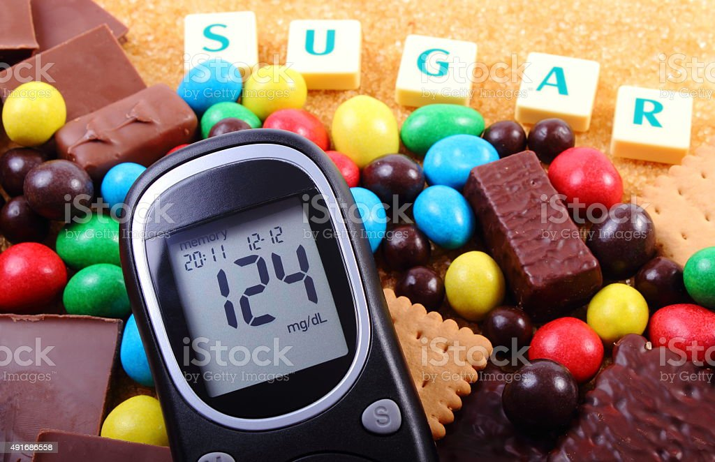 Glucometer, sweets and cane brown sugar with word sugar stock photo