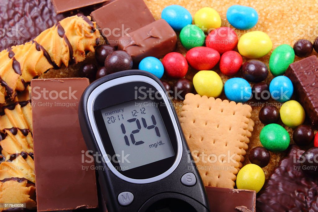 Glucometer with heap of sweets and cane brown sugar stock photo