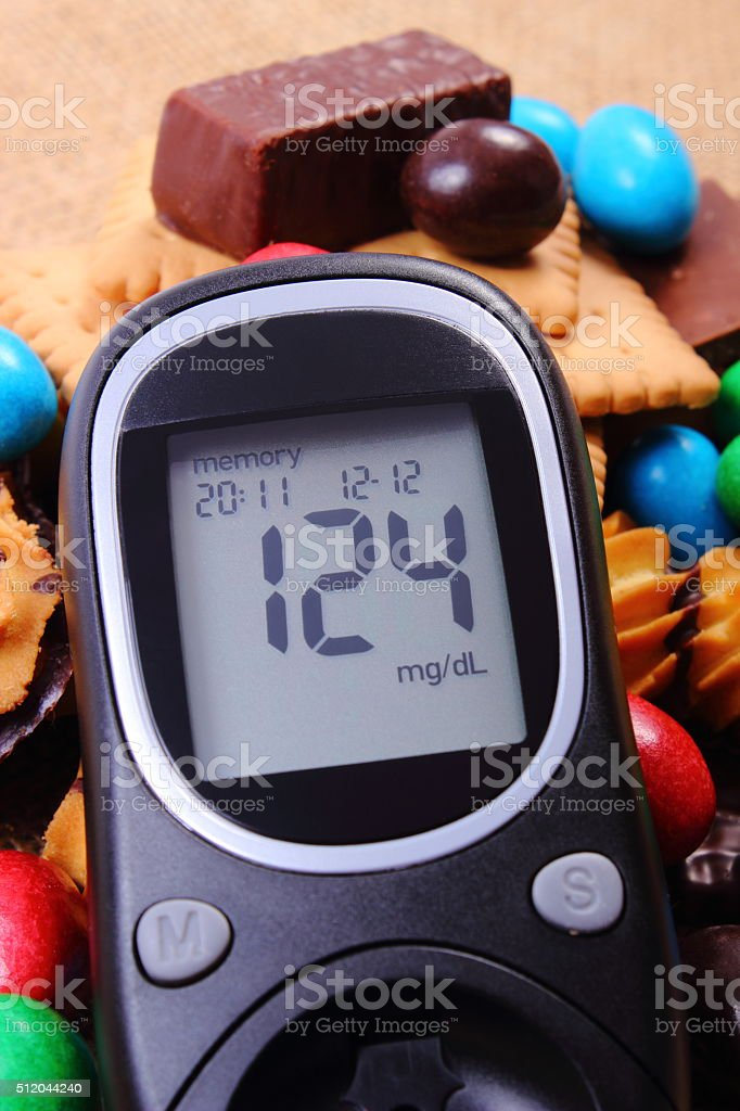 Glucometer with heap of sweets on jute burlap, unhealthy food stock photo