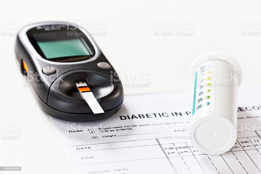 Glucometer with test strips and medical record form royalty-free stock photo