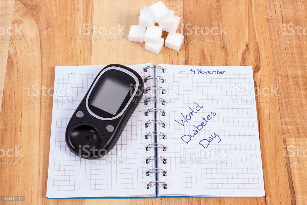 Glucometer, world diabetes day written in notebook and sugar cubes stock photo