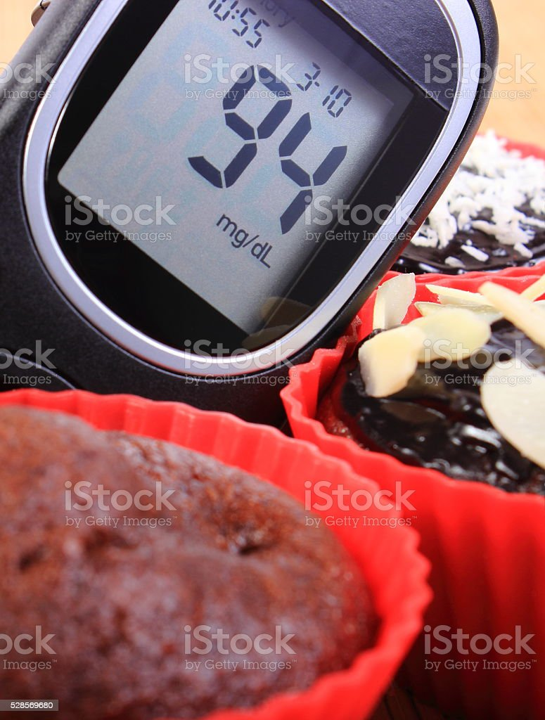 Glucose meter and chocolate muffins in red cups stock photo