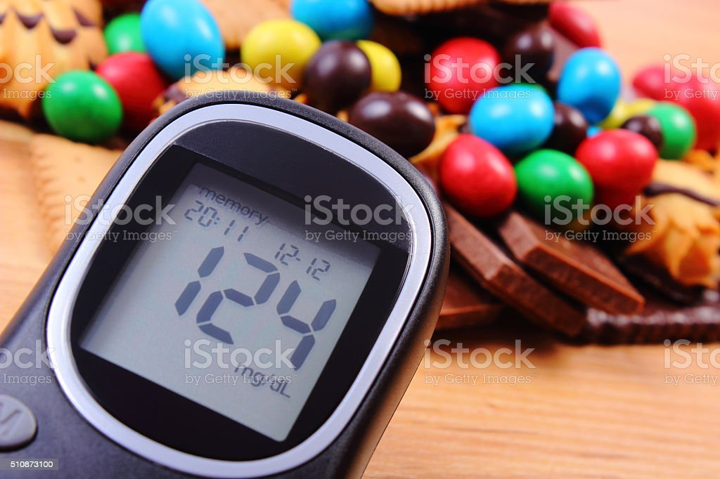 Glucose meter with heap of sweets on wooden surface, diabetes stock photo