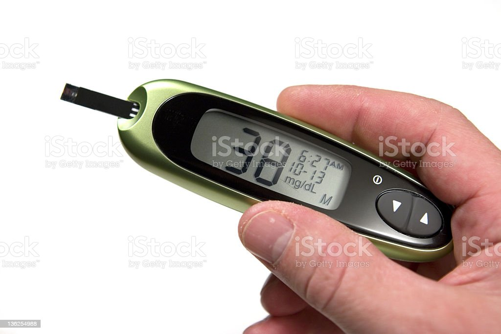 Glucose monitor displaying 38mg/dL being held by a person stock photo