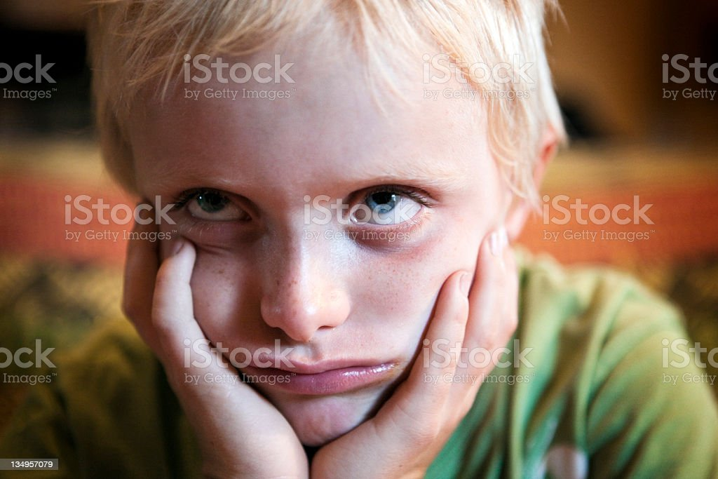 Glum 7 year old boy stock photo