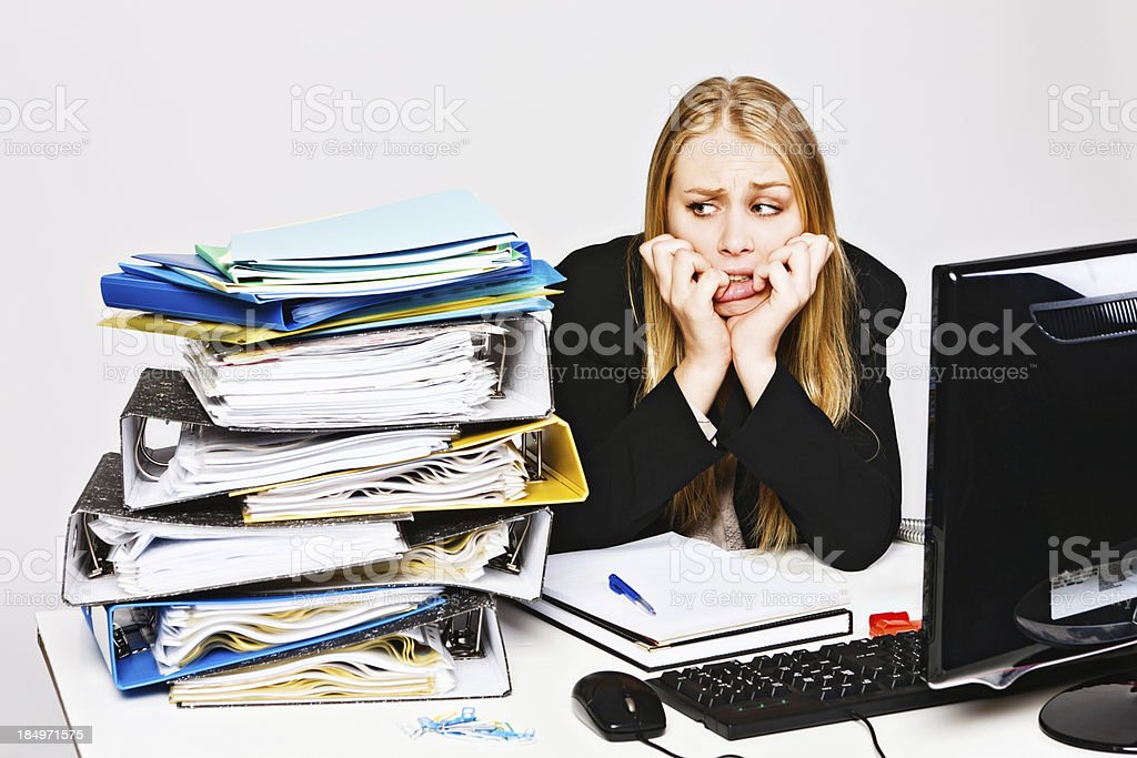 Glum depressed businesswoman biting her nails eyes workload nervously royalty-free stock photo