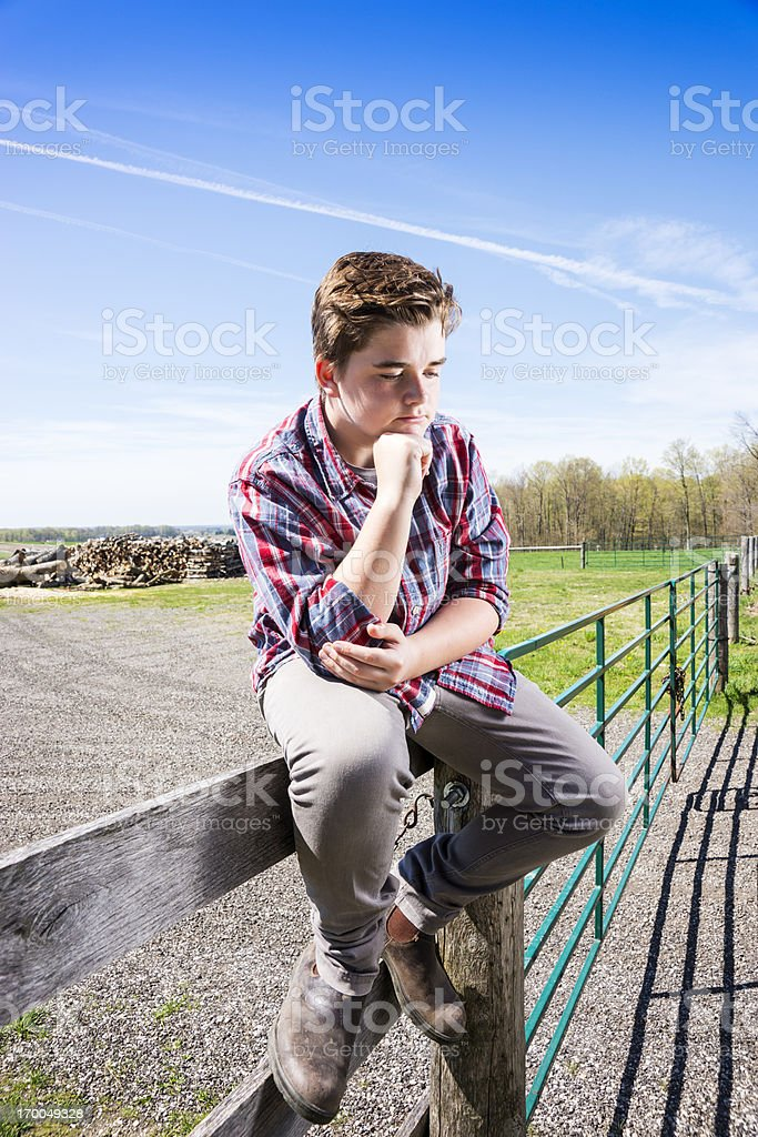 Glum teen boy on a farm royalty-free stock photo