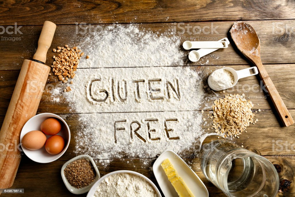 Gluten free bread ingredients and utensils on wood frame background stock photo
