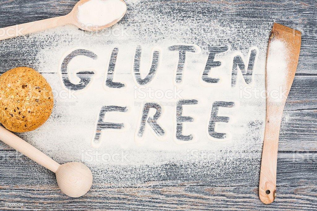 Gluten free word written on flour and wooden table. stock photo