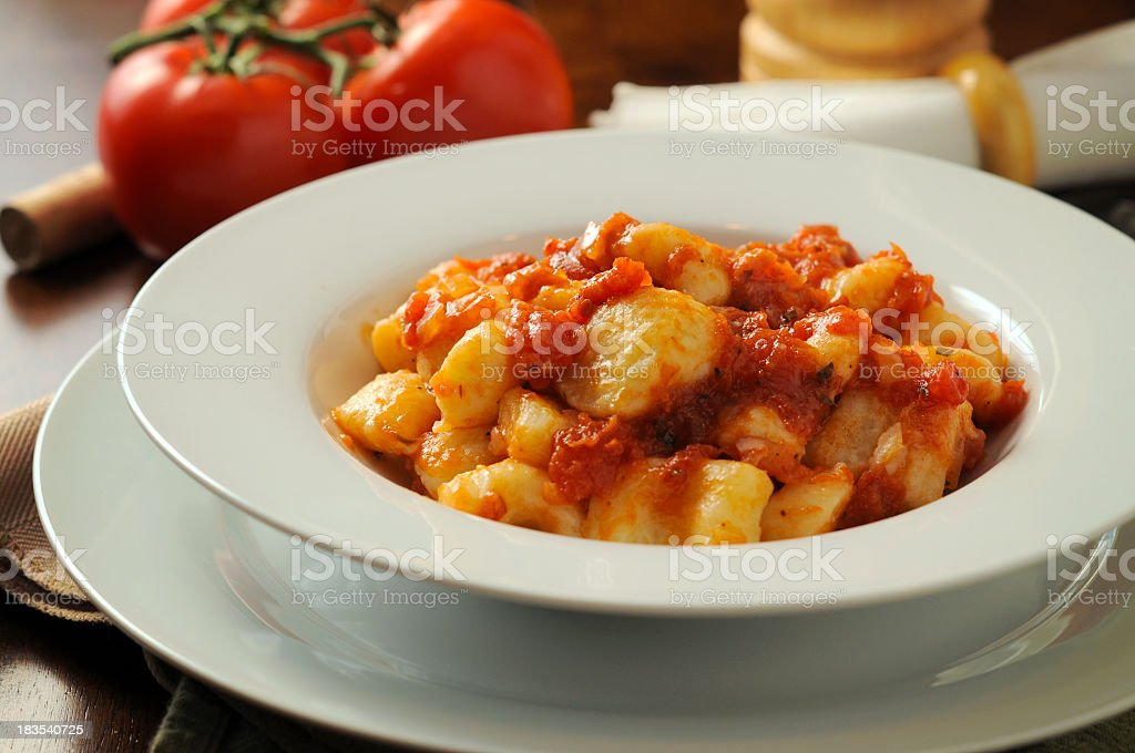 Gnocchi in a white bowl with tomato sauce stock photo
