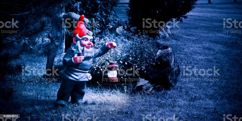 Gnome holding a lantern and smoking a pipe in a blue night stock photo