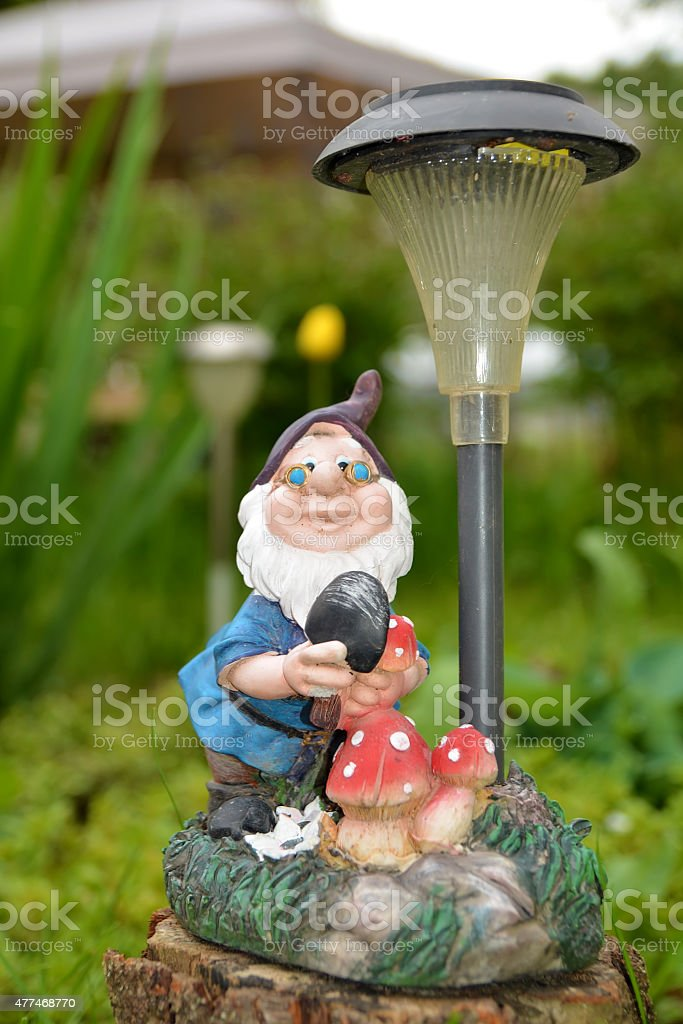 Gnome with garden lamp stock photo