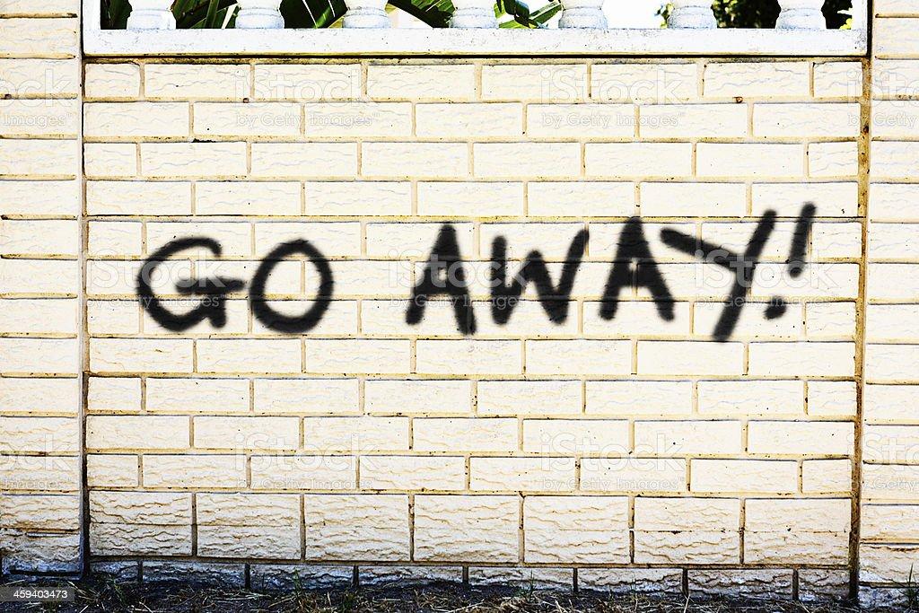 Go Away! says unfriendly graffiti on brick wall stock photo