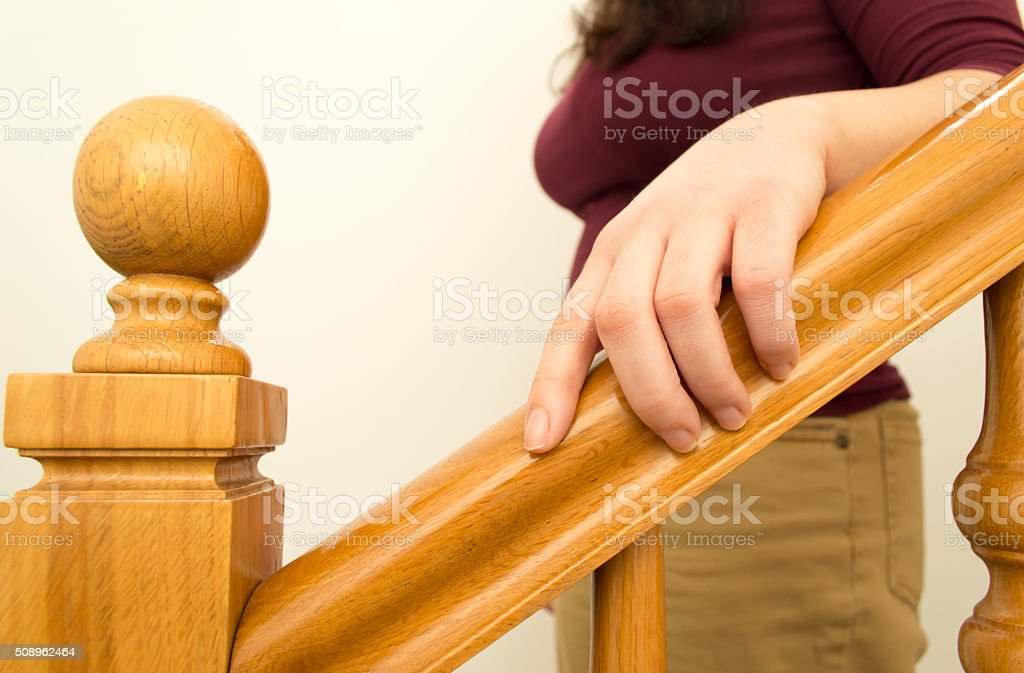 go down the stairs with hand on the railing stock photo