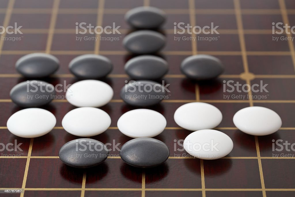 go game playing by stones on wood board stock photo