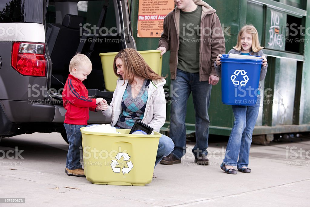 Go Green: Family Unloads Recycle Trash at Recycling Center royalty-free stock photo
