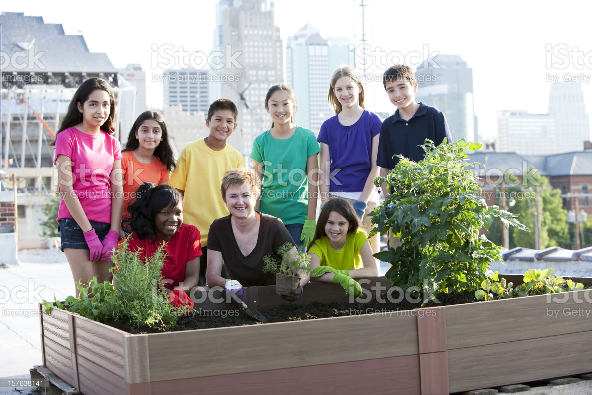 Go Green: Urban Rooftop Garden Planted by Ethnically Diverse Children royalty-free stock photo
