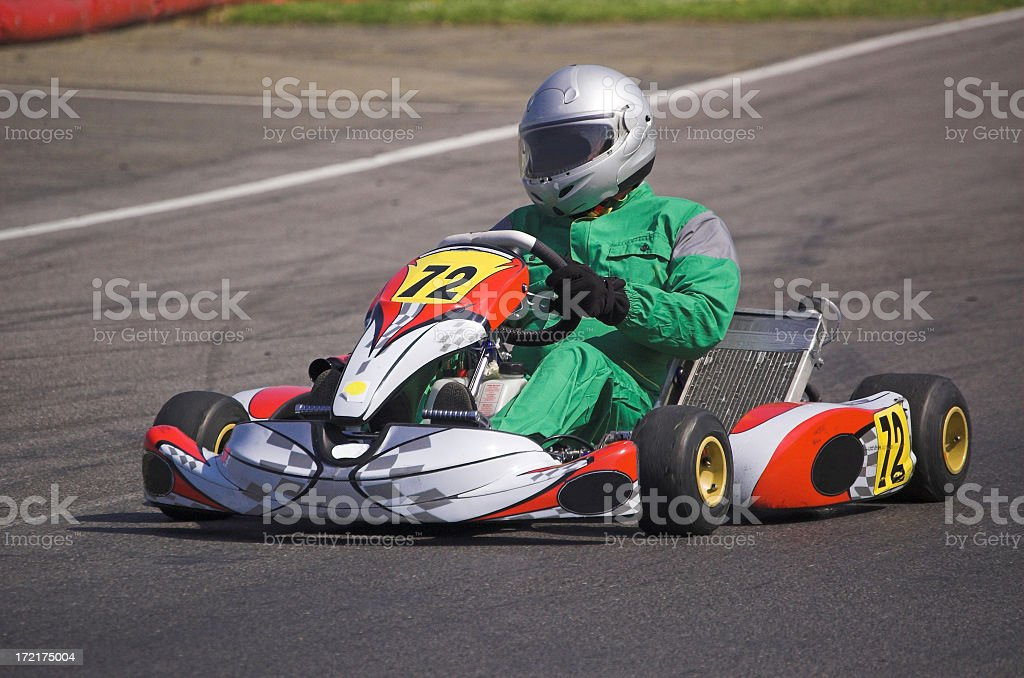 A go kart and driver racing round a track royalty-free stock photo