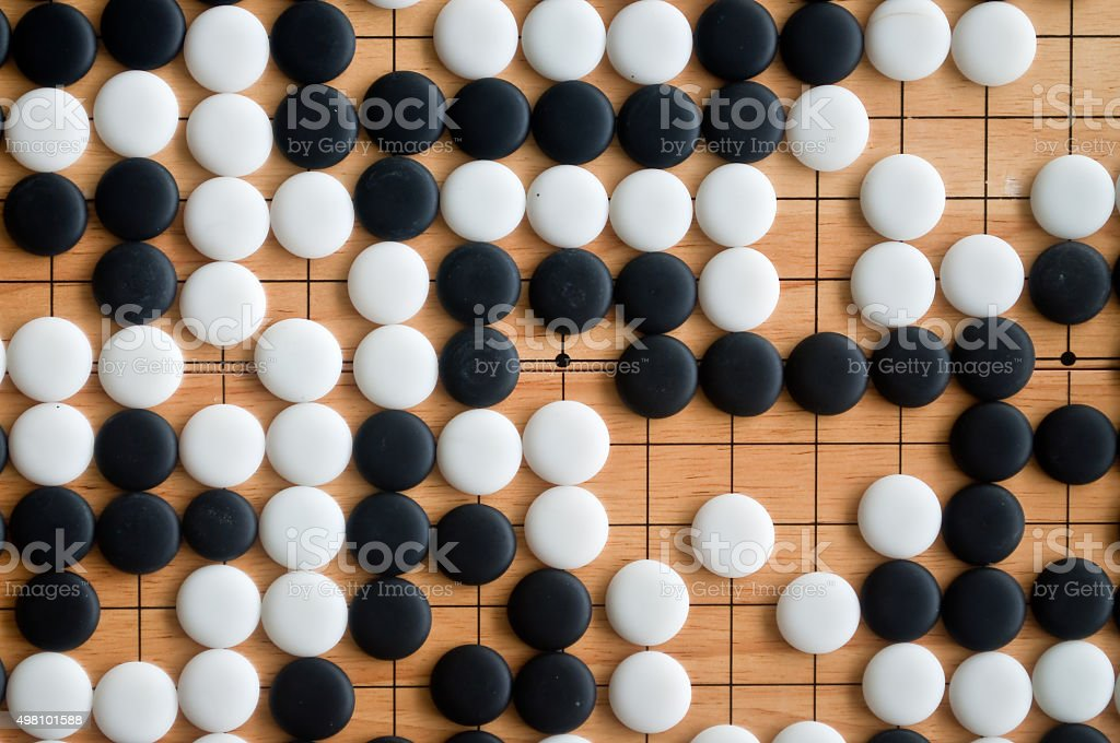 Go pieces on wooden board stock photo