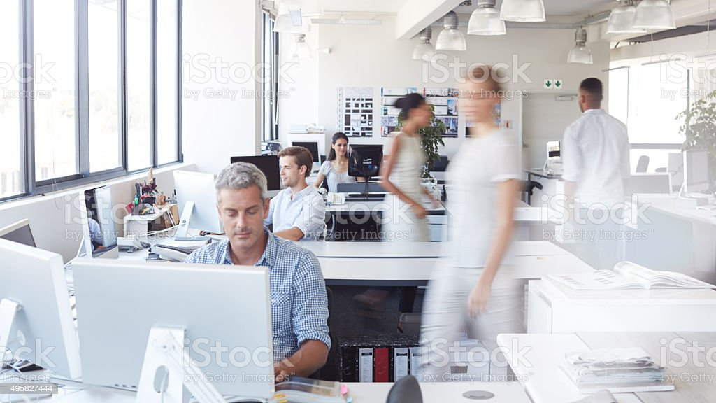 Shot of a man working at his desk with his colleagues blurred in the...
