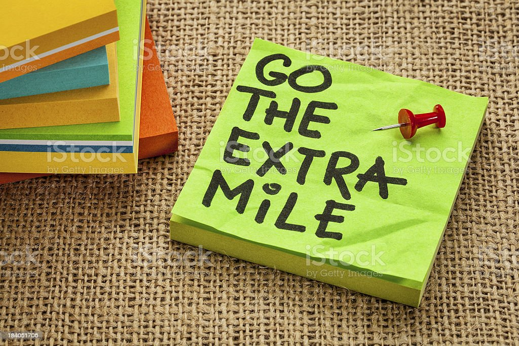 Go the extra mile written on a green post it note stock photo