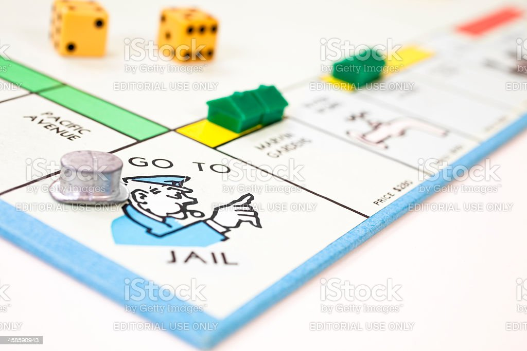 Go to jail on a monopoly board with top hat. stock photo